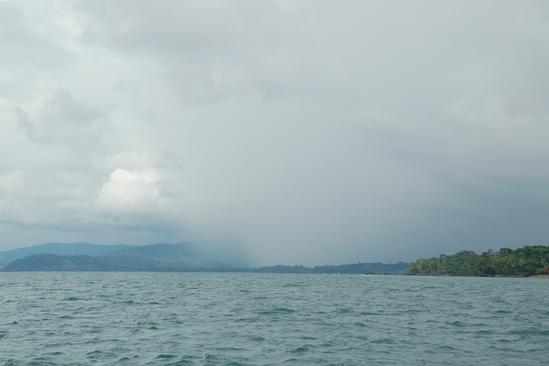 Een gigantische wolkbreuk vult de riviermonding waar wij doorheen moeten..... regenseizoen started!